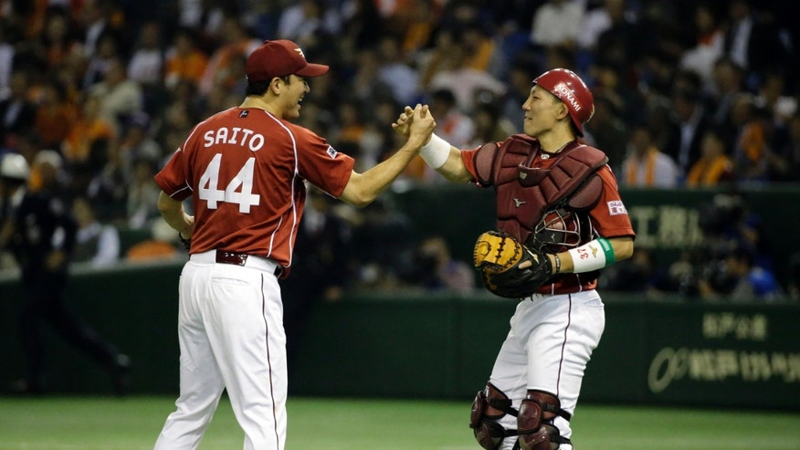 Rakuten Eagles catcher Motohiro Shima, right, celebrates with closer Takashi Saito after beating the Yomiuri Giants 5-1 during Game 3 of baseball's Japan Series at Tokyo Dome in Tokyo, Tuesday, Oct. 29, 2013. (AP Photo/Toru Takahashi)