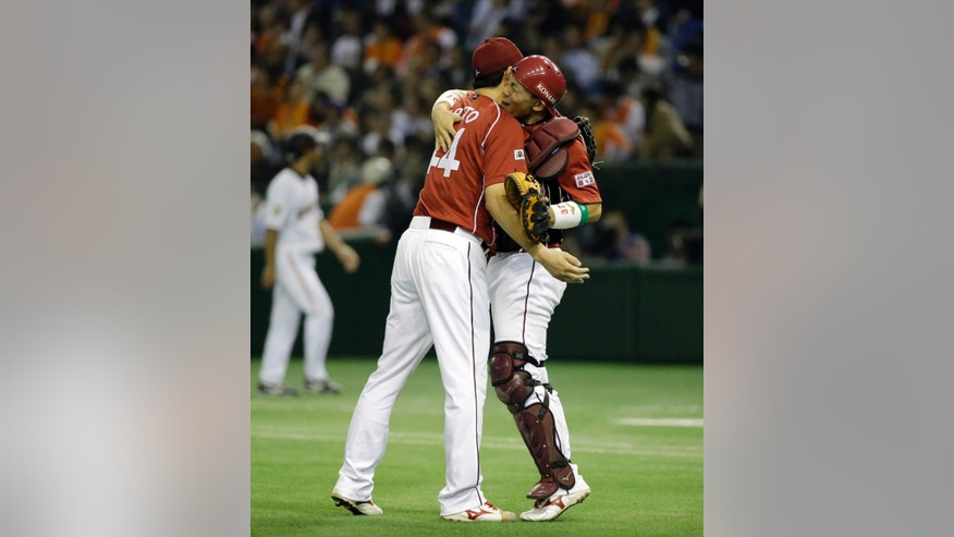 Rakuten Eagles catcher Motohiro Shima, right, celebrates with closer Takashi Saito on the mound after beating the Yomiuri Giants 5-1 during Game 3 of baseball's Japan Series at Tokyo Dome in Tokyo, Tuesday, Oct. 29, 2013. (AP Photo/Toru Takahashi)