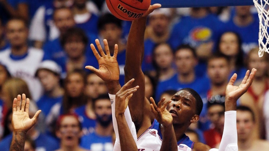 Kansas center Joel Embiid blocks a shot during the first half of an exhibition NCAA college basketball game against Pittsburg State in Lawrence, Kan., Tuesday, Oct. 29, 2013. (AP Photo/Orlin Wagner)
