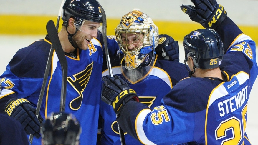 St. Louis Blues goalie Jaroslav Halak, center, of Slovakia, is congratulated by teammates Alex Pietrangelo (27) and Chris Stewart (25) after the Blues' 3-2 victory over the Winnipeg Jets in an NHL hockey game Tuesday, Oct. 29, 2013, in St. Louis. (AP Photo/Bill Boyce)