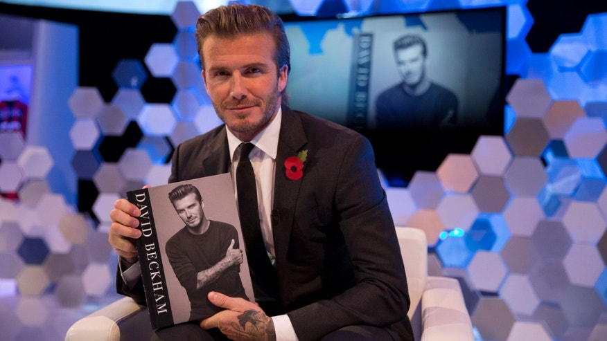 "Former England national soccer team captain David Beckham poses for photographs with a copy of his new photography book entitled ""David Beckham"" after being interviewed by The Associated Press at a studio in Hampstead, north London, Wednesday, Oct. 30, 2013.  (AP Photo/Matt Dunham)"