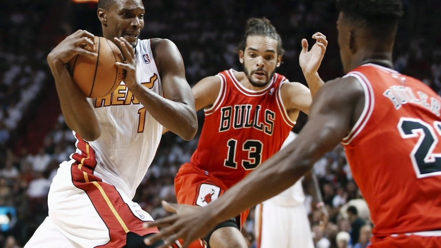Miami Heat's Chris Bosh (1) tries to drive between Chicago Bulls' Joakim Noah (13) and Jimmy Butler (22) during the first half of an NBA basketball game in Miami, Tuesday, Oct. 29, 2013. (AP Photo/J Pat Carter)