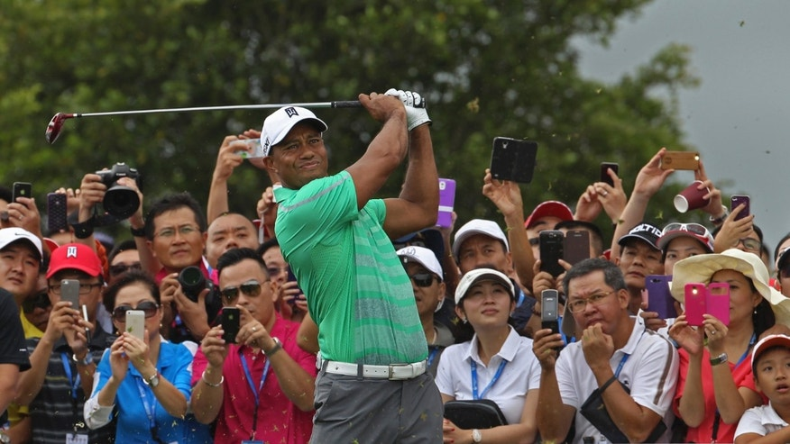 Tiger Woods of the United States tees off during an exhibition golf match against Rory Mcllory of Northern Ireland in Haikou, in southern China's island province Hainan, Monday, Oct. 28, 2013. (AP Photo/Vincent Yu)