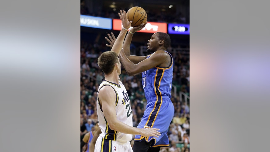 Oklahoma City Thunder's Kevin Durant, right, shoots as Utah Jazz's Gordon Hayward defends in the first quarter of an NBA basketball game Wednesday, Oct. 30, 2013, in Salt Lake City.  (AP Photo/Rick Bowmer)
