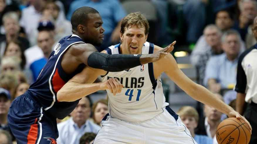Dallas Mavericks' Dirk Nowitzki (41), of Germany, fights off Atlanta Hawks' Paul Millsap as he looks for a shot opportunity in the first half of an NBA basketball game Wednesday, Oct. 30, 2013, in Dallas. (AP Photo/Tony Gutierrez)