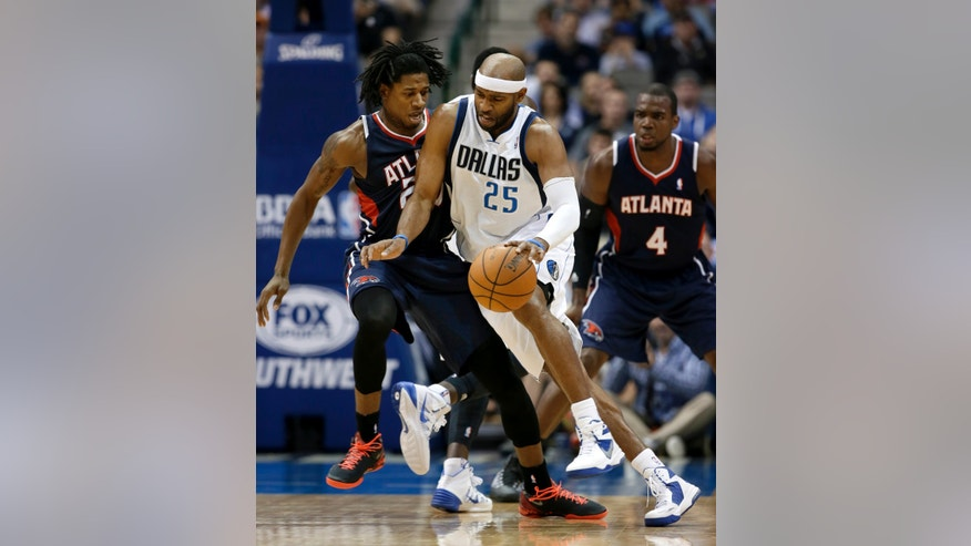 Atlanta Hawks forward Cartier Martin, left, falls back as Dallas Mavericks guard Vince Carter (25) attempts to drive around him in the first half of an NBA basketball game Wednesday, Oct. 30, 2013, in Dallas. (AP Photo/Tony Gutierrez)