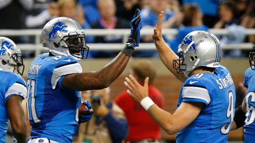 Detroit Lions wide receiver Calvin Johnson, left, celebrates his 2-yard touchdown reception with quarterback Matthew Stafford (9) during the first half of an NFL football game in Detroit, Sunday, Oct. 27, 2013. (AP Photo/Duane Burleson)