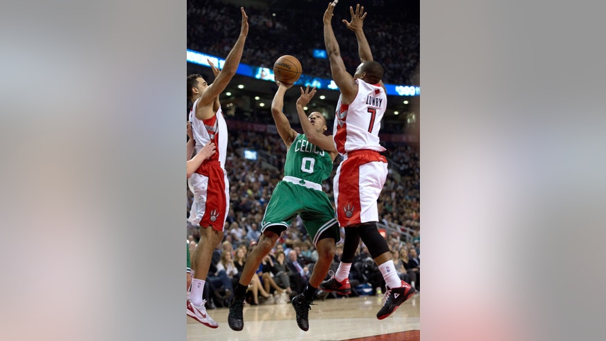 Boston Celtics guard Avery Bradley (0) shoots under pressure from Toronto Raptors forward Landry Fields, left, and guard Kyle Lowry during the first half of an NBA basketball game Wednesday, Oct. 30, 2013, in Toronto. (AP Photo/The Canadian Press, Frank Gunn)