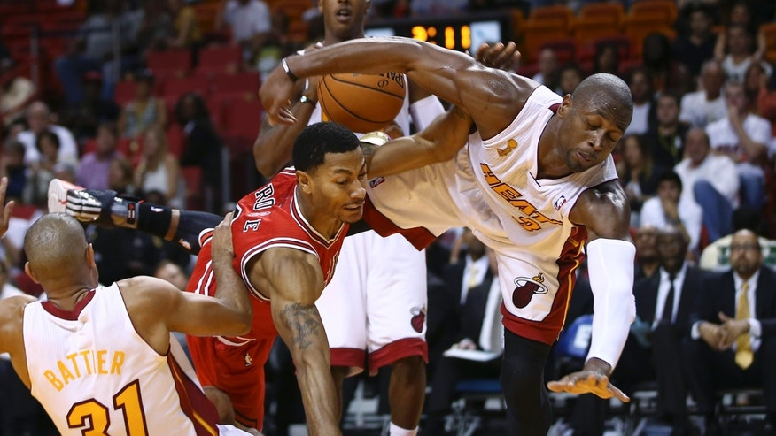 After blocking a shot by Chicago Bulls' Derrick Rose (1), Miami Heat's Dwyane Wade (3) falls to the court during the second half of a NBA basketball game in Miami, Tuesday, Oct. 29, 2013. The Heat won 107-95. (AP Photo/J Pat Carter)