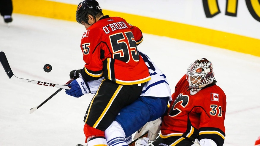 Toronto Maple Leafs' Carter Ashton, center, gets caught between Calgary Flames' Shane O'brien, left, and goalie Karri Ramo, from Finland, during the second period of an NHL hockey game in Calgary, Alberta, Wednesday, Oct. 30, 2013. (AP Photo/The Canadian Press, Jeff McIntosh)