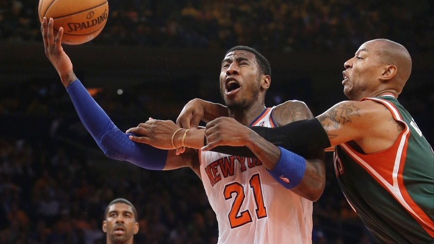 Milwaukee Bucks' Caron Butler, right, fouls New York Knicks' Iman Shumpert during the first half of an NBA basketball game Wednesday, Oct. 30, 2013, in New York. (AP Photo/Frank Franklin II)