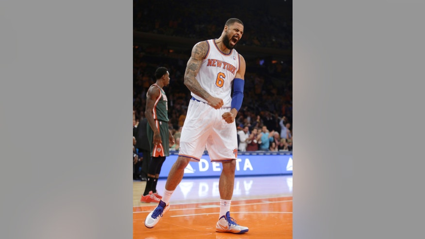 New York Knicks' Tyson Chandler reacts after dunking the ball during the first half of an NBA basketball game Wednesday, Oct. 30, 2013, in New York. At left is Milwaukee Bucks' Larry Sanders. (AP Photo/Frank Franklin II)