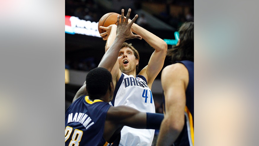 Dallas Mavericks power forward Dirk Nowitzki puts up a shot over his former Mavericks teammate Indiana Pacers center Ian Mahinmi (28) in the first half of a preseason NBA basketball game, Friday, Oct. 25, 2013 in Dallas. (AP Photo/The Dallas Morning News, Tom Fox)  MANDATORY CREDIT; MAGS OUT; TV OUT; INTERNET USE BY AP MEMBERS ONLY; NO SALES