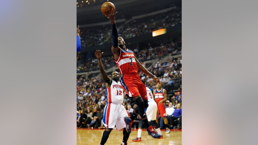Washington Wizards guard John Wall (2) drives to the basket past Detroit Pistons guard Will Bynum (12) during the first half of an NBA basketball game in Auburn Hills, Mich., Wednesday, Oct. 30, 2013. (AP Photo/Paul Sancya)