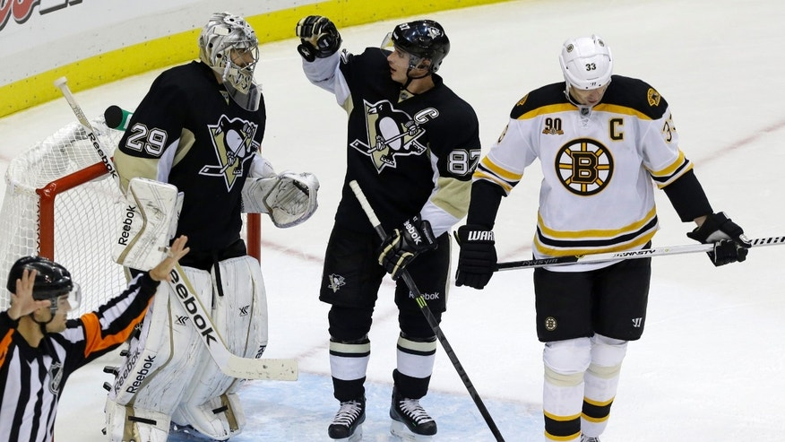 Pittsburgh Penguins goalie Marc-Andre Fleury (29) celebrates with Sidney Crosby (87) as Boston Bruins'  Zdeno Chara (33) skates off the ice at the end of an NHL hockey game in Pittsburgh on Wednesday, Oct. 30, 2013. The Penguins won 3-2. (AP Photo/Gene J. Puskar)