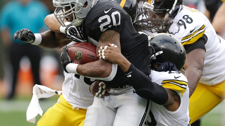 Oakland Raiders running back Darren McFadden (20) runs for a 7-yard touchdown past Pittsburgh Steelers strong safety Troy Polamalu, rear, free safety Ryan Clark, bottom right, and defensive tackle Vance Walker (98) during the first quarter of an NFL football game in Oakland, Calif., Sunday, Oct. 27, 2013. (AP Photo/Ben Margot)