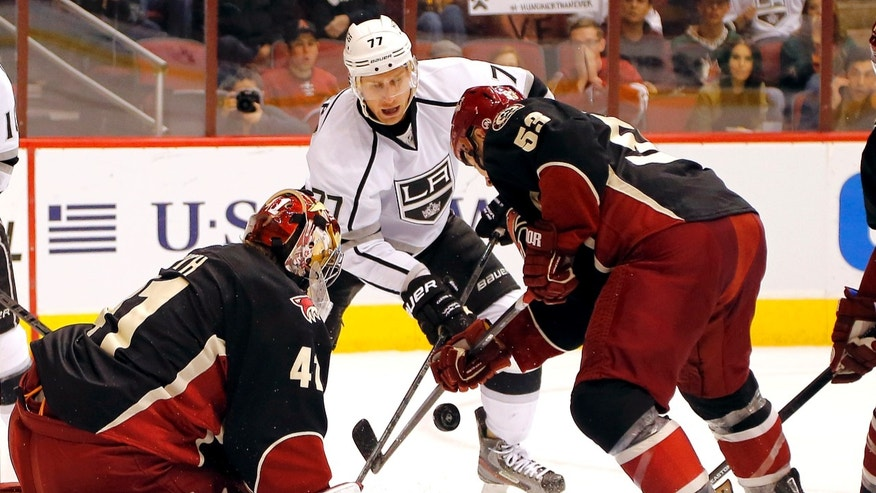 Phoenix Coyotes' Derek Morris, right, and goalie Mike Smith, left, try to keep the puck from Los Angeles Kings' Jeff Carter during the first period of an NHL hockey game, Tuesday, Oct. 29, 2013, in Glendale, Ariz. (AP Photo/Matt York)