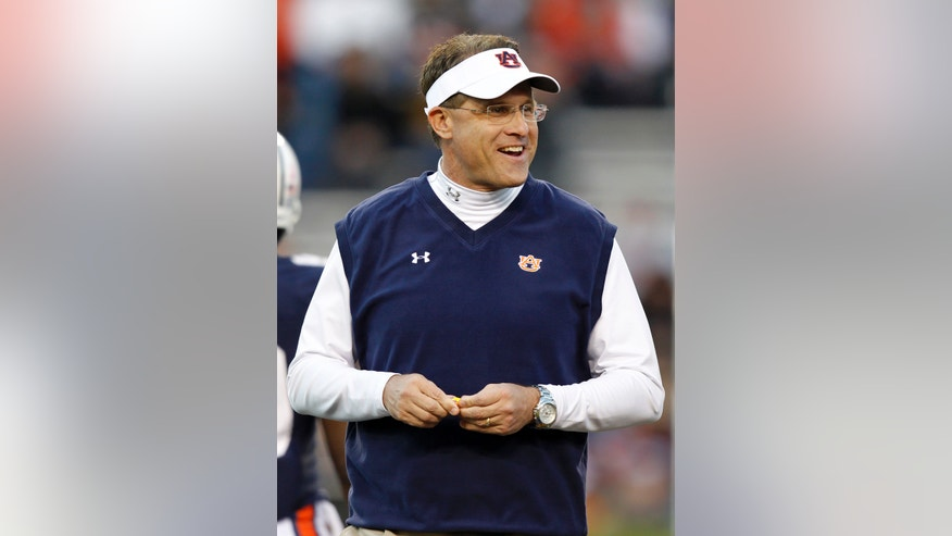 File-This Oct. 26, 2013 file photo shows Auburn head coach Gus Malzahn walking around before  the first half of an NCAA college football game against Florida Atlantic in Auburn, Ala.  Arkansas head coach Bret Bielema engaged in some back-and-fort with Malzahn during the summer about the pace of college offenses. The two will finally meet on the field this week when the surging Tigers visit the Razorbacks, losers of five straight who are coming off a bye. (AP Photo/Butch Dill, File)