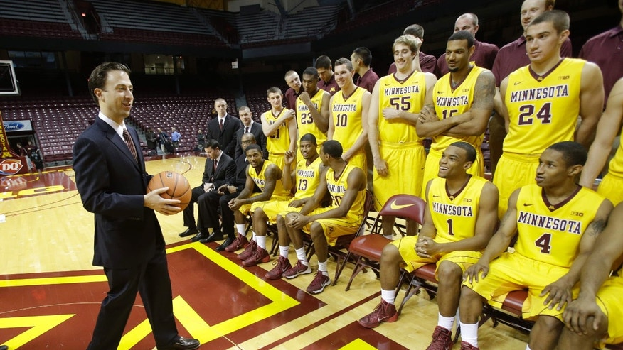 New Minnesota head basketball coach Richard Pitino, left, looks at his players before joining them for a team photo on media day, Monday, Oct. 28, 2013, in Minneapolis. (AP Photo/Jim Mone)