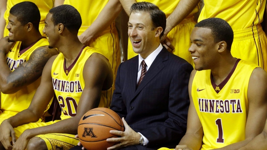 New Minnesota head basketball coach Richard Pitino, center, enjoys a laugh along with, from left, Maverick Ahanmisi, Austin Hollins and right, Andre Hollins (no relation) during set up for the formal team portrait during media day, Monday, Oct. 28, 2013, in Minneapolis. (AP Photo/Jim Mone)