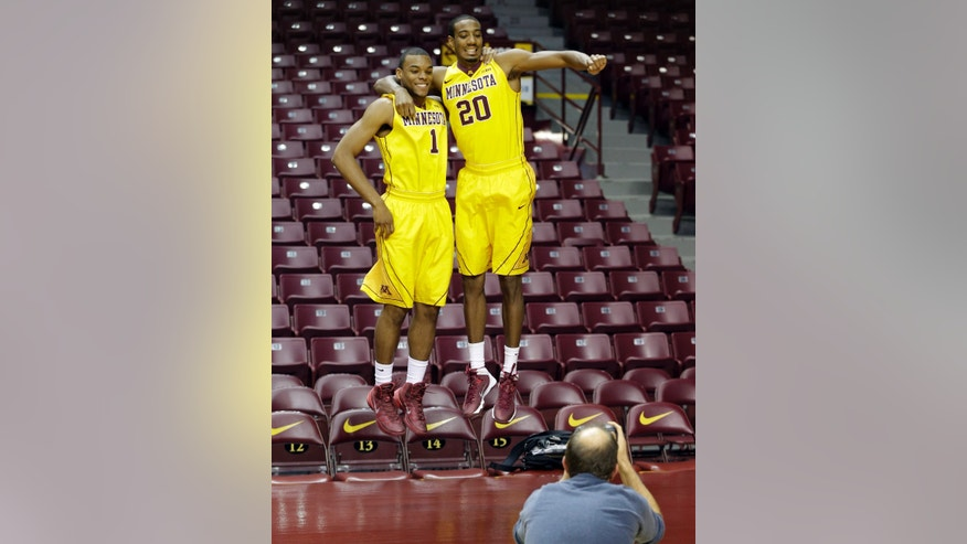 Minnesota basketball players Andre Hollins, left, and Austin Hollins (no relation) do a double jump for a photographer on media day, Monday, Oct. 28, 2013, in Minneapolis. (AP Photo/Jim Mone)