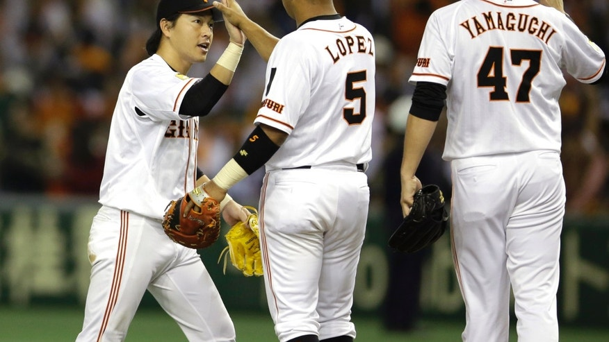 Yomiuri Giants center fielder Hisayoshi Chono, left, celebrates with teammates Javier Lopez (5) and closer Tetsuya Yamaguchi (47) after beating the Rakuten Eagles 6-5 in Game 4 of baseball's Japan Series at Tokyo Dome in Tokyo, Wednesday, Oct. 30, 2013. (AP Photo/Toru Takahashi)