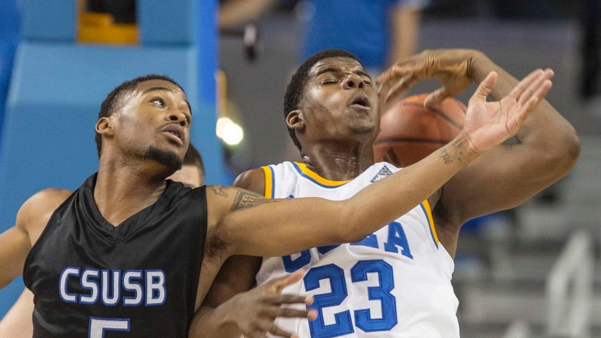 UCLA's Tony Parker (23) and Cal State San Bernardino's Donte Medder(5) battle for a loose ball in the first half of an NCAA college exhibition  basketball game on Wednesday, Oct. 30, 2013, in Los Angeles. (AP Photo/Ringo H.W. Chiu)
