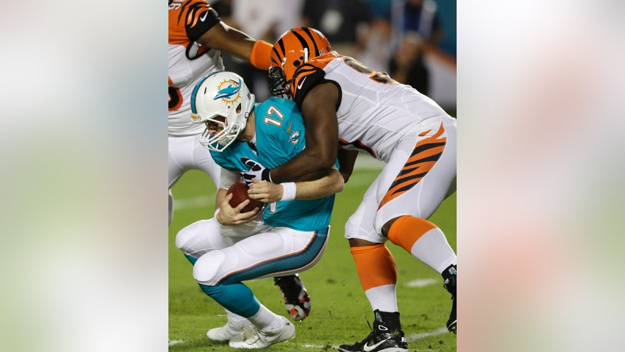 Miami Dolphins quarterback Ryan Tannehill (17) is sacked by Cincinnati Bengals defensive tackle Geno Atkins during the first half of an NFL football game, Thursday, Oct. 31, 2013, in Miami Gardens, Fla. (AP Photo/Wilfredo Lee)