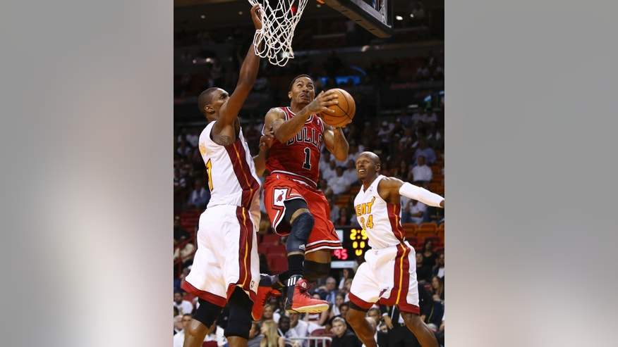 Chicago Bulls' Derrick Rose (1) goes to the basket between Miami Heat's Chris Bosh (1) and Ray Allen (34) during the second half of an NBA basketball game in Miami, Tuesday, Oct. 29, 2013. Rose missed the shot. The Heat won 107-95. (AP Photo/J Pat Carter)