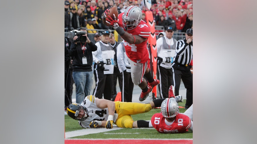 FILE - In this Oct. 19, 2013 file photo, Ohio State running back Carlos Hyde, top, dives over the goal line to score a touchdown  during an NCAA college football game against Iowa in Columbus, Ohio. After being suspended for the first three games of the season, Hyde is trying to make up for lost time. So far, he's made up a lot of ground. (AP Photo/Jay LaPrete, File)