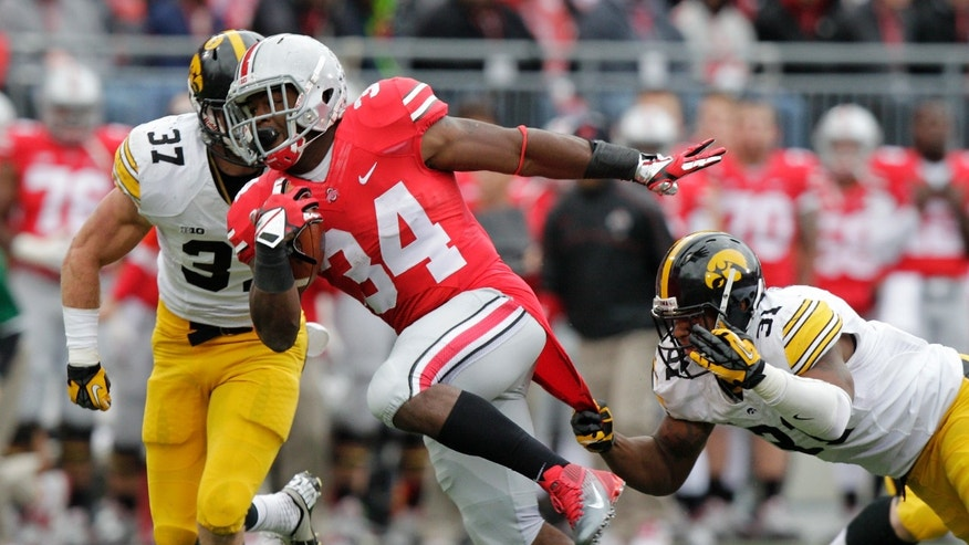 FILE - In this Oct. 19, 2013 file photo, Ohio State running back Carlos Hyde (34) runs between Iowa defenders John Lowdermilk, left, and Anthony Hitchens during  an NCAA college football game in Columbus, Ohio. After being suspended for the first three games of the season, Hyde is trying to make up for lost time. So far, he's made up a lot of ground. (AP Photo/Jay LaPrete, File)