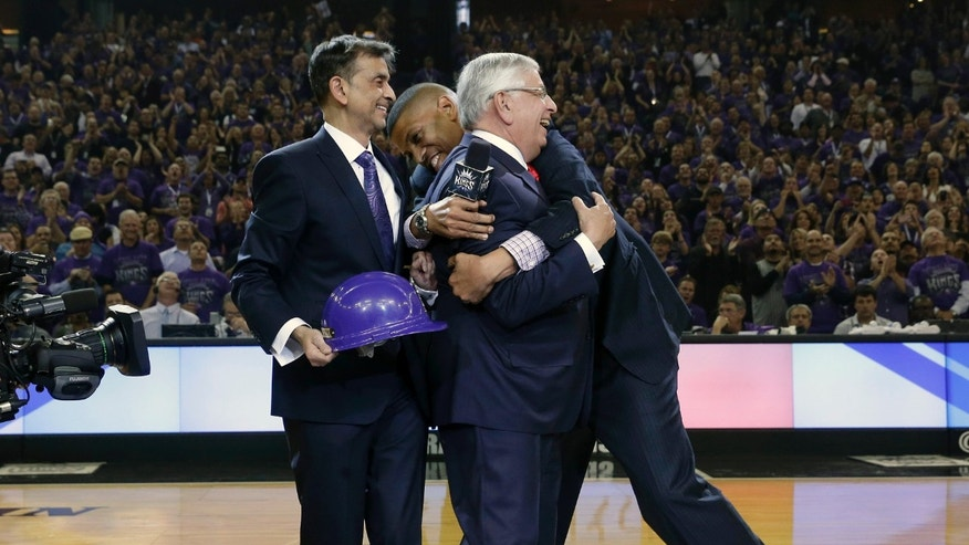 Sacramento Mayor Kevin Johnson, right, hugs NBA Commissioner David Stern as Kings majority owner Vivek Ranadive, left, watches during ceremonies in a NBA basketball game against the Denver Nuggets in Sacramento, Calif., Wednesday, Oct. 30, 2013. Ceremonies were held to celebrate Ranadive's purchase of the team from the Maloof family. (AP Photo/Rich Pedroncelli)