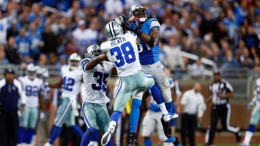 Detroit Lions wide receiver Calvin Johnson (81) catches a 54-yard reception against Dallas Cowboys cornerback Brandon Carr (39) and defensive back Jeff Heath (38) in the fourth quarter of an NFL football game in Detroit, Sunday, Oct. 27, 2013. (AP Photo/Rick Osentoski)