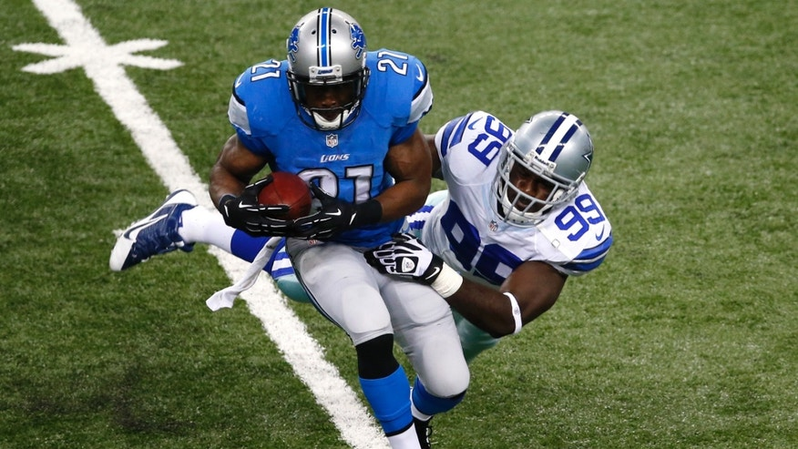 Detroit Lions running back Reggie Bush (21) is brought down by Dallas Cowboys defensive end George Selvie (99) in the first half of an NFL football game in Detroit, Sunday, Oct. 27, 2013. (AP Photo/Paul Sancya)