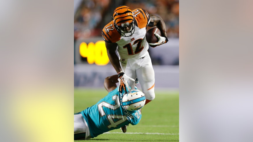 Miami Dolphins cornerback Dimitri Patterson (24) tackles Cincinnati Bengals wide receiver Mohamed Sanu (12) during the first half of an NFL football game, Thursday, Oct. 31, 2013, in Miami Gardens, Fla. (AP Photo/Wilfredo Lee)