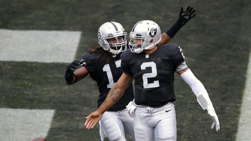 Oakland Raiders quarterback Terrelle Pryor (2) celebrates with wide receiver Denarius Moore after running for a 93-yard touchdown against the Pittsburgh Steelers during the first quarter of an NFL football game in Oakland, Calif., Sunday, Oct. 27, 2013. (AP Photo/Marcio Jose Sanchez)