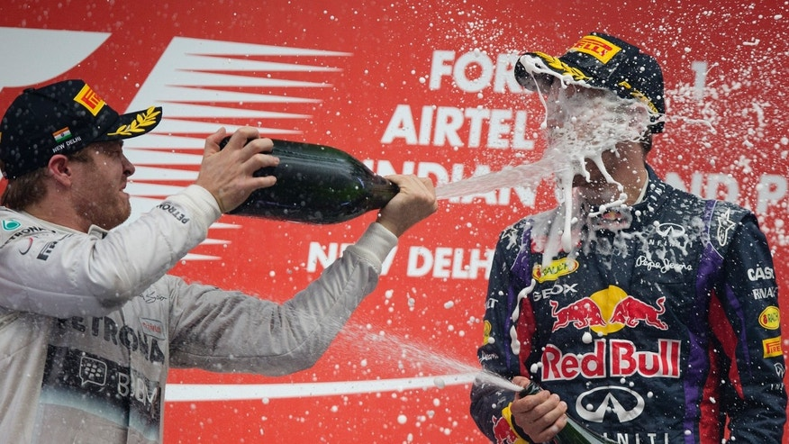 Red Bull driver Sebastian Vettel of Germany -is sprayed with champagne by compatriot and second placed Mercedes driver Nico Rosberg after winning the Indian Formula One Grand Prix and his 4th straight F1 world drivers championship at the Buddh International Circuit in Noida, India, Sunday, Oct. 27, 2013. (AP Photo/Mark Baker)