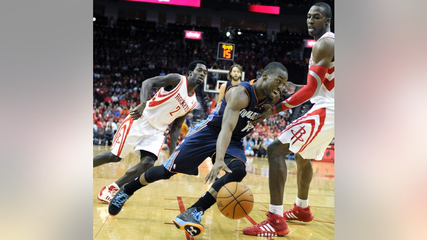 Charlotte Bobcats' Kemba Walker, center, drives the ball between Houston Rockets Patrick Beverley (2) and Dwight Howard in the first half of an NBA basketball game Wednesday, Oct. 30, 2013, in Houston. (AP Photo/Pat Sullivan)