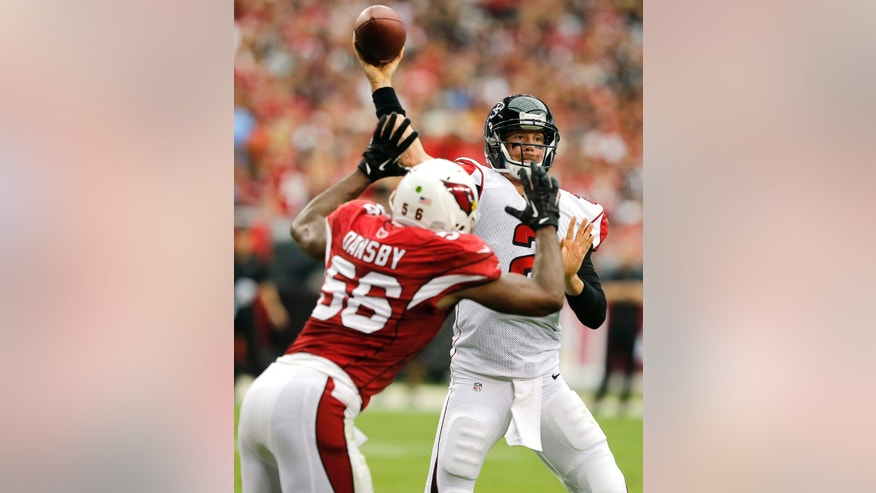 Atlanta Falcons quarterback Matt Ryan, right, throws over Arizona Cardinals inside linebacker Karlos Dansby (56) during the first half of an NFL football game Sunday, Oct. 27, 2013, in Glendale, Ariz. (AP Photo/Rick Scuteri)