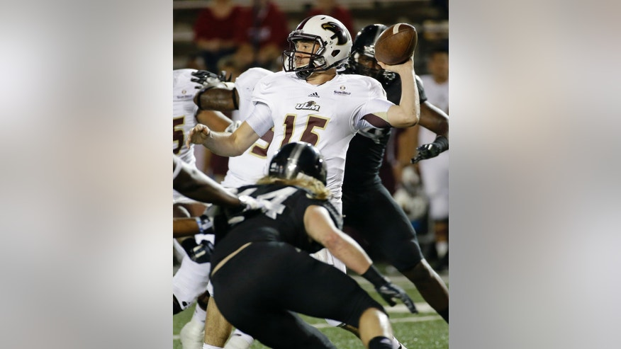 Louisiana Monroe quarterback Kolton Browning (15) looks for a receiver as he is pressured by Troy defensive end Tyler Roberts, bottom, during the first half of an NCAA college football game in Troy, Ala., Thursday, Oct. 31, 2013. (AP Photo/Dave Martin)