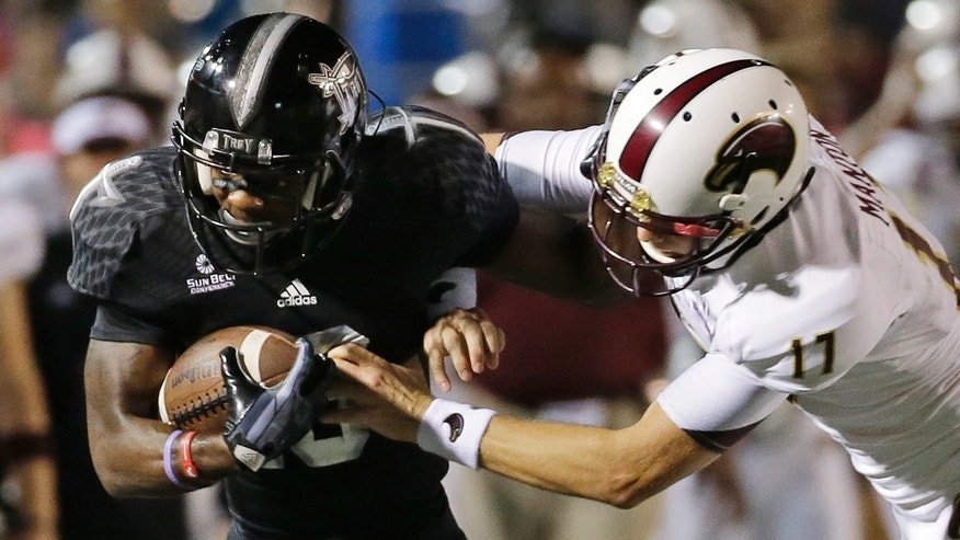 Troy wide receiver Bryan Holmes, left, is knocked out of bounds by Louisiana Monroe kicker Justin Manton (17) during the first half of an NCAA college football game in Troy, Ala., Thursday, Oct. 31, 2013. (AP Photo/Dave Martin)