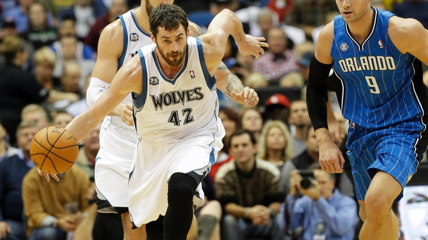 Minnesota Timberwolves' Kevin Love, left, beats Orlando Magic' Nikola Vucevic, of Montenegro, to the ball in the first quarter of an NBA basketball game, Wednesday, Oct. 30, 2013 in Minneapolis. (AP Photo/Jim Mone)