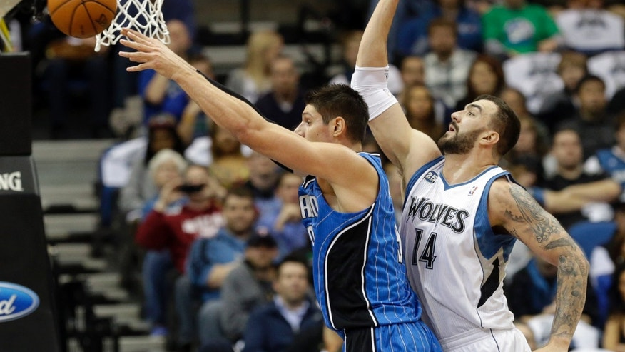 Orlando Magic' s Nikola Vucevic, left, of Montenegro, gets off a pass as Minnesota Timberwolves' Nikola Pekovic, of Montenegro, defends in the first quarter of an NBA basketball game, Wednesday, Oct. 30, 2013 in Minneapolis. (AP Photo/Jim Mone)