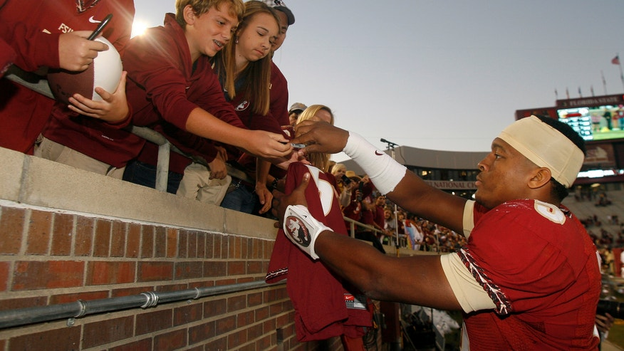 Florida State quarterback Jameis Winston, right, signs autographs for fans in the final seconds of the fourth quarter of an NCAA college football game against North Carolina State, Saturday, Oct. 26, 2013, in Tallahassee, Fla. Florida State won 49-17. (AP Photo/Phil Sears)