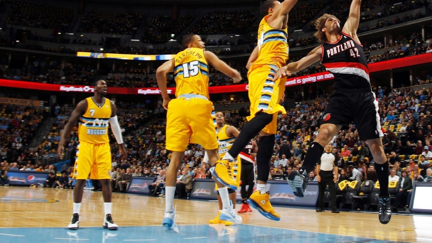 Portland Trail Blazers center Robin Lopez, right, drives lane for a shot past Denver Nuggets center JaVale McGee, third from left, and forwards Anthony Randolph, second from left, and J.J. Hickson in the first quarter of an NBA basketball game in Denver on Friday, Nov. 1, 2013. (AP Photo/David Zalubowski)