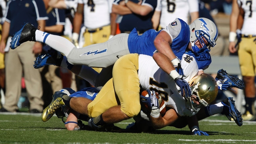 Notre Dame tight end Ben Koyack, front bottom, is tackled by Air Force linebacker Joey Nichol, front top, and defensive back Gavin McHenry, back, after receiving a pass in the first quarter of an NCAA college football game in Air Force Academy, Colo., Saturday, Oct. 26, 2013. (AP Photo/David Zalubowski)
