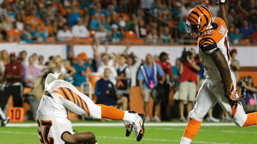 Cincinnati Bengals running back Gio Bernard (25) rolls head-first for a touchdown during the second half of an NFL football game against the Miami Dolphins, Thursday, Oct. 31, 2013, in Miami Gardens, Fla. At right is wide receiver Mohamed Sanu (12). (AP Photo/Lynne Sladky)
