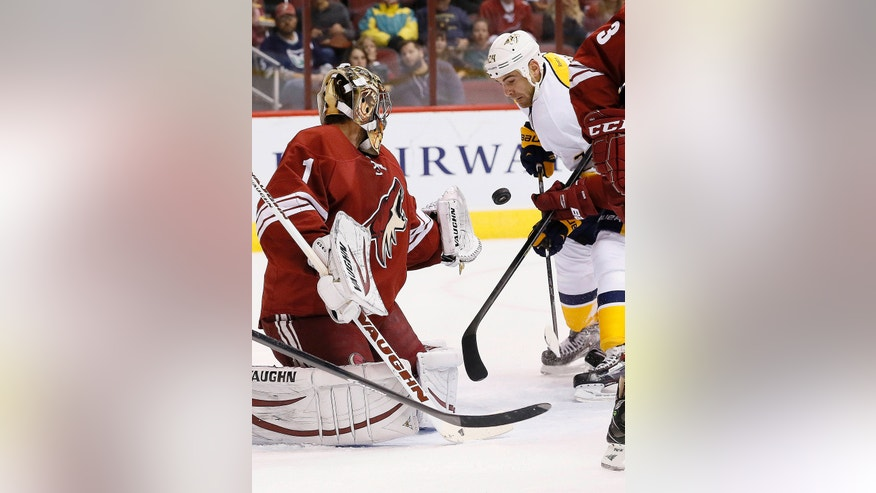 Nashville Predators' Eric Nystrom (24) flips the puck past Phoenix Coyotes' Thomas Greiss (1), of Germany, for a goal during the first period of an NHL hockey game Thursday, Oct. 31, 2013, in Glendale, Ariz. (AP Photo/Ross D. Franklin)
