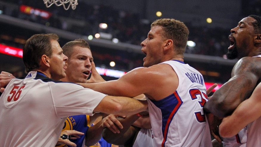 Referee Mark Ayotte, left, breaks up a scuffle between Los Angeles Clippers center DeAndre Jordan, right, and Golden State Warriors Andrew Bogut (not shown) with  Clippers forward Blake Griffin, center, trying to keep the peace with Warriors forward David Lee, second from left, in the second quarter during an NBA basketball game on Thursday, Oct. 31, 2013, in Los Angeles. (AP Photo/Alex Gallardo)