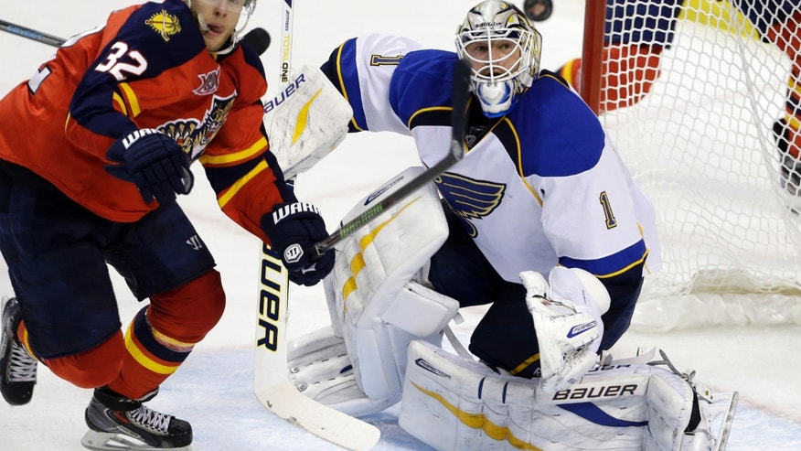 St. Louis Blues goalie Brian Elliott (1) and Florida Panthers right wing Kris Versteeg watch the puck during the second period of an NHL hockey game Friday, Nov. 1, 2013, in Sunrise, Fla. (AP Photo/Lynne Sladky)